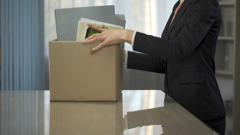 Businesswoman unpacking stuff from box onto her new office desk, employment Footage