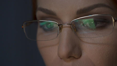 Female working on laptop, screen reflection in eyeglasses, busy face close-up Footage