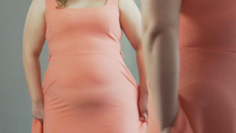 Woman pulling back dress and looking at her flabby stomach reflected in mirror Footage