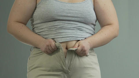 Fat lady putting efforts to button and zip her pants, weight problems, dieting Footage