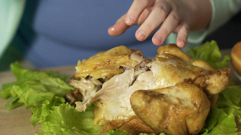 Overweight woman tearing pieces of meat from roast chicken, eating with hands Live Action