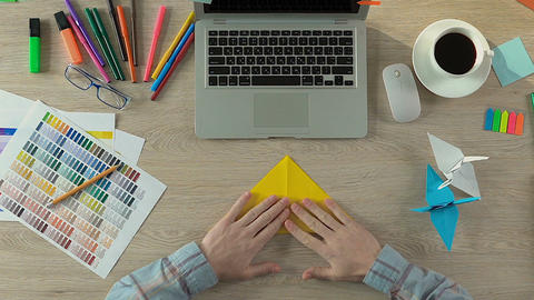 Creative man folding origami at workspace, meditation and inspiration, handcraft Live Action