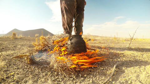 Man warms tea in a kettle on a fire from a dry grass on background Dry mountaino Live Action