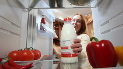 View from Fridge Woman Opens Door Takes Milk and Sits at Table Footage