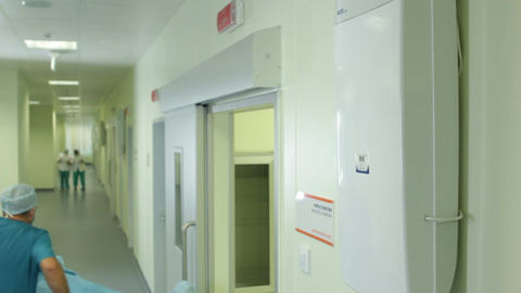 Lift Door Opens and Doctor Transports Patient along Hall Footage