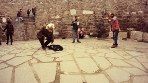 Turkish gypsies play music in courtyard of citadel Hisar tourists walk listen An Live Action