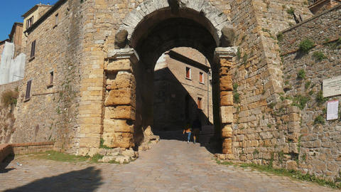Couple walking below the Porta dell'Arco arch in Volterra Footage