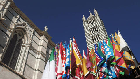 Flags of the Palio di Siena in front of the cathedral, Tuscany, Italy Footage