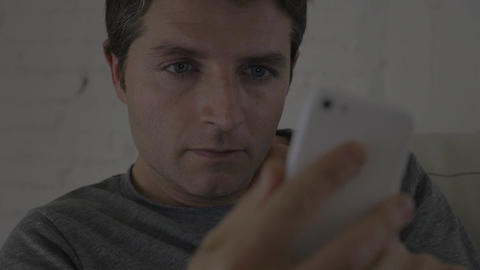 close up shot young attractive man with blue eyes at home relaxed texting on mob ビデオ