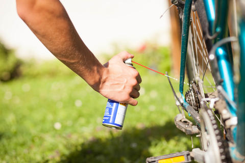 Young man using spray oil for his bike; maintenance フォト