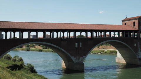 Panoramic view of old covered bridge on Ticino river in Pavia, Italy Footage