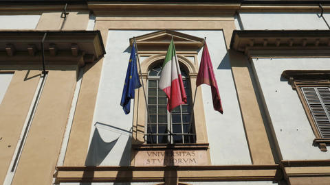University, Italian and European flags waving above the entrance of Pavia Univer Footage