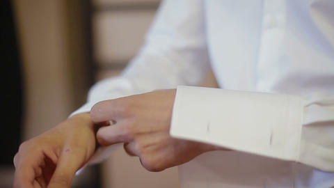 Close up of a mans grooms hand while fastening cuff Footage