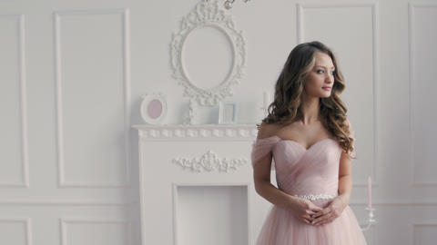 Beautiful brunette girl wearing in pink wedding dress in classic hall Footage