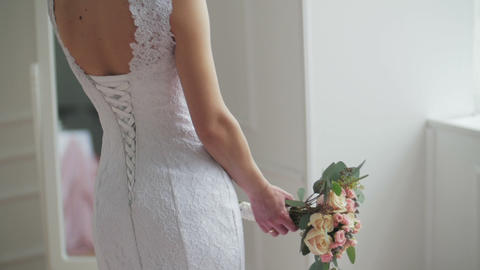 Beautiful young bride in stylish wedding gown standing near mirror Footage