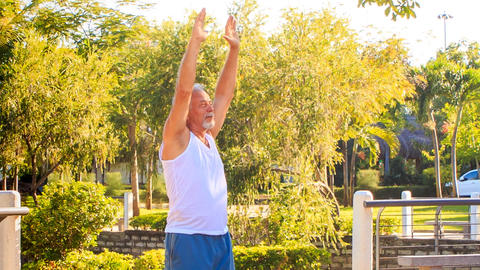 Old Man Does Morning Exercises Turns Right Left in Park Footage