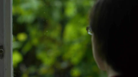 black haired woman looks out the window in the yard with green vegetation 1 Footage