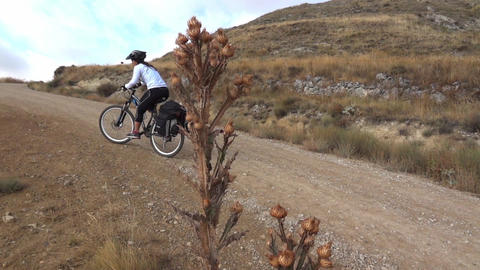 Cyclists hardly climb a steep slope, on the bike, on the road of land bordered b Footage