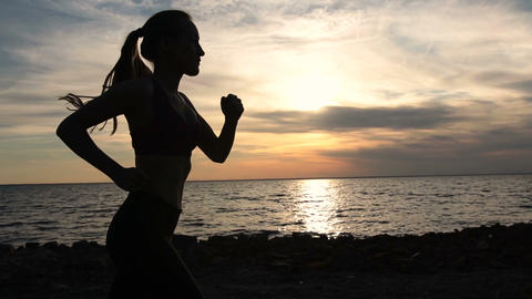 Young fitness woman jogging on seaside at sunset Footage