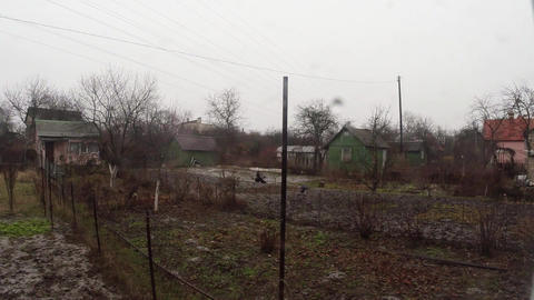 Snow falls on empty vegetable gardens, small houses and crows Footage