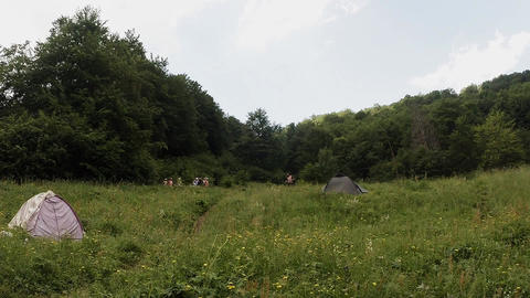 A guy with dreadlocks runs past tents in the woods amidst the walking children o Footage