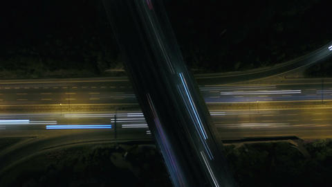 Static vertical top down aerial view of traffic on freeway interchange at night Archivo