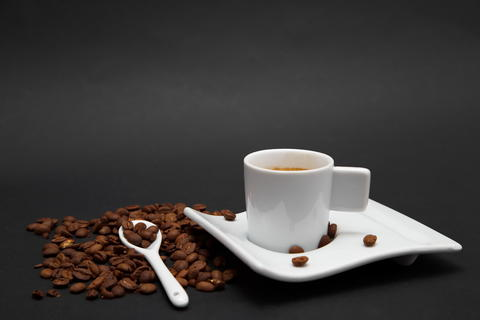 Cup of Coffee and coffee beans on black background Foto