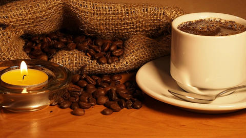 romantic background with candles, a cup of coffee and coffee beans in a bag. a c Footage