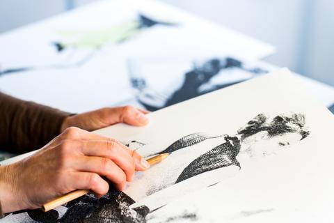 Female hand making fashion sketch フォト