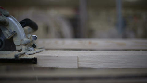 A carpenter saws off a board with a disk saw Footage