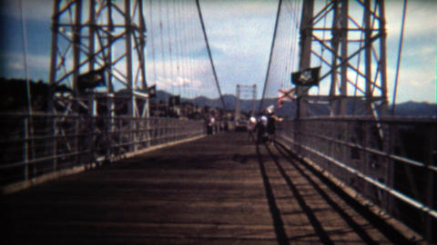 1972: People walking across bridge on windy day, flags blowing Footage
