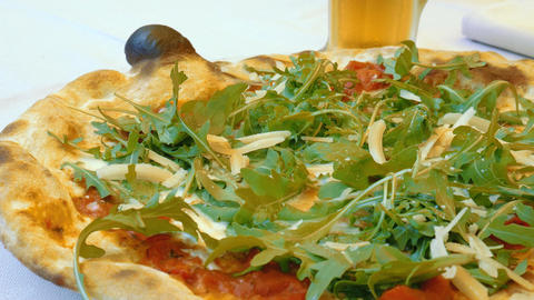 Cutting Italian Pizza topped with parmesan cheese and delicious arugula Footage
