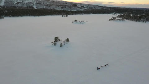 Drone flight over a dog sled crossing a frozen lake 画像