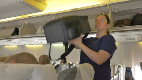 Video of woman putting luggage to overhead cabin on the airplane in 4K Live Action