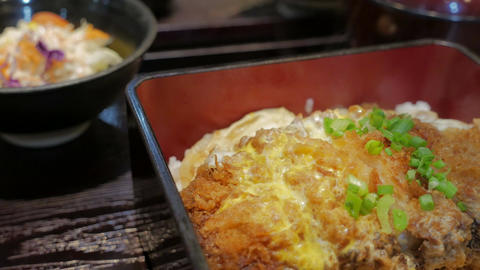 Japanese cuisine Katsudon. Fried Pork with egg, onion on rice Live Action