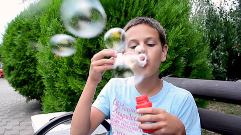 Happy teenager blowing soap bubbles in spring park Footage