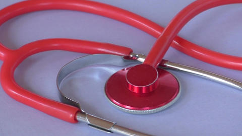 A red medical stethoscope. Medical instrument for listening Live Action