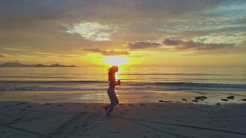 Girl Silhouette Jogs on Wet Beach against Rising Sun Reflection Footage