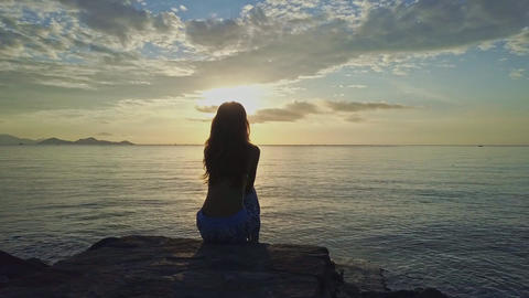 Girl Silhouette Sits on Beach Rock Watches Bright Sunrise Footage