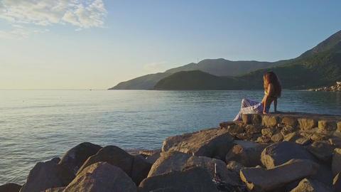 Flycam Moves behind Blond Girl against Azure Ocean Green Hills Footage