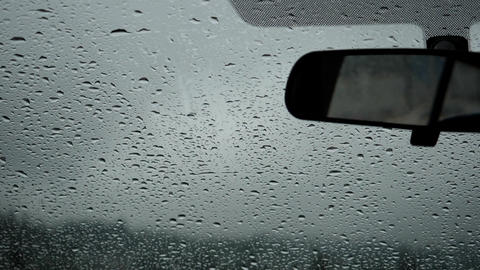 Slow motion of rainy day view during car windshield wipers rain drops sliding do Footage