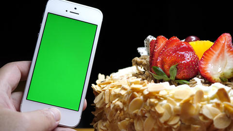 Motion of fruit birthday cake and hand holding green screen phone on a black bac Live Action