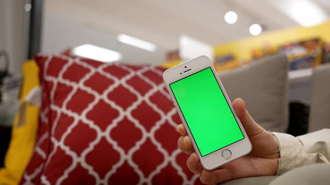 Motion of woman holding green screen mobile phone on sofa with bokeh 4k shopping Footage