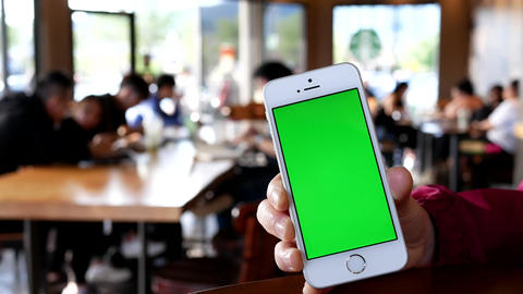 Hand holding green screen iphone inside Starbucks store with 4k resolution Footage