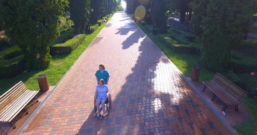 Aerial footage of caregiver walking with disabled senior in wheelchair Footage
