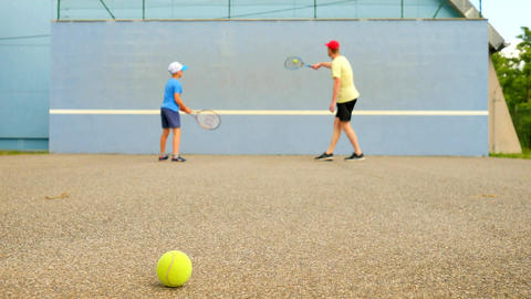 Father and son practice tennis at training wall. Hobby players with racket and b Live Action