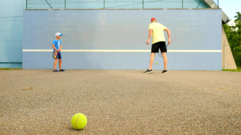 Back of adult man and kid learn tennis while beat off balls from green wall Footage