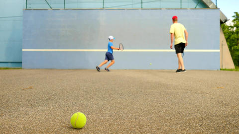 Back of adult man and kid learn tennis while beat off... Stock Video Footage
