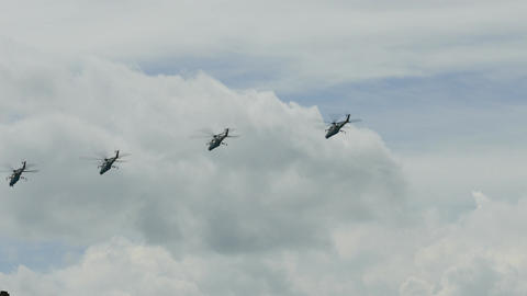 4K Ungraded: Group of Four Attack Helicopter Gunships Flies in Blue Cloudy Sky Footage