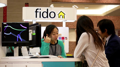 People asking fido sales clerk about cellphone plan inside Burnaby shopping mall Image